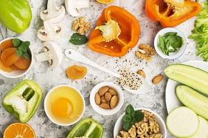 Ingredients for healthy seasonal feeding of green, orange and white flowers: cucumber, zucchini, egg, mushrooms, dried apricots, sweet peppers, oranges, quinoa, almonds, walnut, mint, frisee salad. Top view. Copy space.