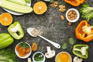 Ingredients for healthy seasonal feeding of green, orange and white flowers: cucumber, zucchini, mushrooms, dried apricots, sweet peppers, oranges, quinoa, almonds, walnut, mint, frisee salad Top view Copy space. Against a dark background