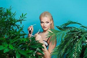 Young woman among palm trees