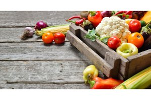 Raw organic set of fresh vegetables in wooded box background. Autumn harvest from the garden, long banner