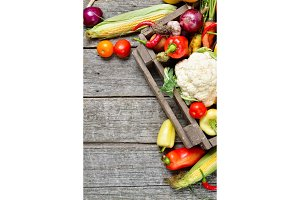 Vertical Raw organic set of fresh vegetables in wooded box background. Autumn harvest from the garden