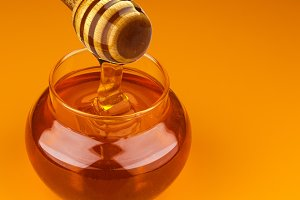Honey stick and bowl of pouring honey isolated on yellow background
