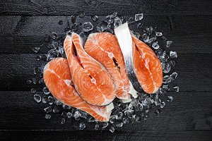 Salmon steaks on black wooden table top view