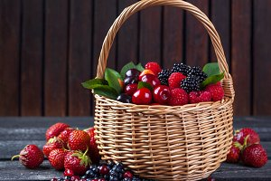 Berries mix in basket on rustic wooden background