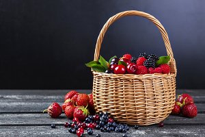 Fresh forest berries in basket on dark background