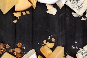Frame of different types of cheese on black table