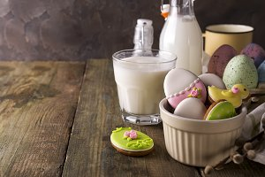 Plate with colourful Easter cookies and glass of milk, rustic style