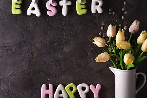 Lettering from cookies Happy Easter and bouquet tulips on stone background.