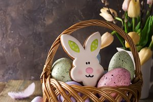Colorful easter eggs and cookies bunny in basket and tulips flowers on wooden table.