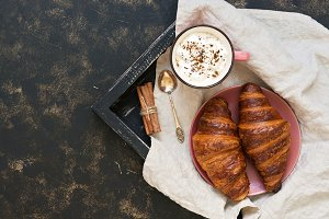 Croissants and coffee with marshmallow on wooden tray with napkin, dark rustic background. Top view, copy space.