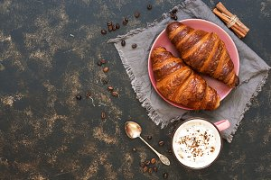 Breakfast with croissants and coffee on a rustic background. French pastry. The view from the top,space for text.