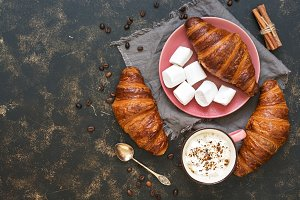 Marshmallows, coffee and fresh croissants on a dark background. Top view, copy space. French food.