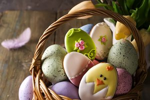 Colorful easter eggs and cookies in basket and tulips flowers on wooden table.