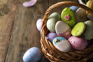 Colorful easter eggs and cookies icing as egg in basket on wooden table.