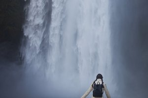 girl runs to the skogafoss waterfall