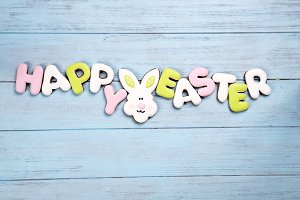 Happy Easter colorful lettering Happy Easter of ginger biscuits and cookies bunny on wooden blue background.