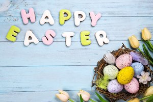 Beautiful e tulips with colorful eggs in nest on blue wooden background and cookies lettering Happy Easter