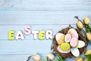 Beautiful e tulips with colorful eggs in nest on blue wooden background and cookies lettering Easter