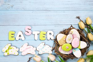 Beautiful e tulips with colorful eggs in nest and cookies as bunny on blue wooden background and cookies lettering Happy Easter