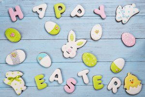 Colorful Easter cookies and lettering Happy Easter all over blue wooden background.