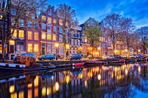 Amterdam canal, boats and medieval houses in the evening