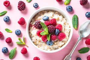 Oatmeal cereal with milk and berries top view.