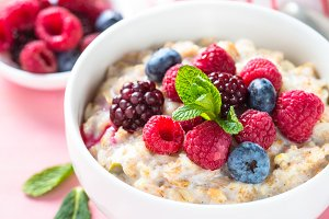 Oatmeal porrige with milk and berries close up.