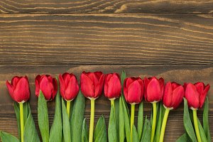 Row of tulips on wooden background with space for message. Mother's Day background. Top view