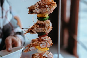 Shrimps oe prawns served on a vertical skewer in an restaurant