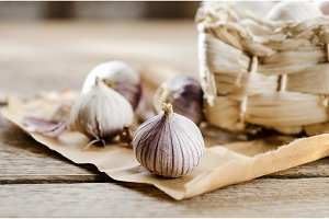 Basket with small heads of garlic on wooden background on kraft paper