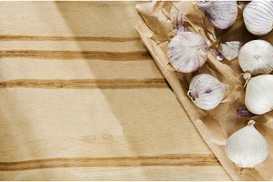 Small heads of garlic scattered on wooden background on kraft paper
