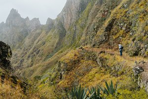 Traveler with camera in front of the monumental mountain ridge and ravine on the cobbled path to Xo-Xo Valley. Santo Antao Island, Cape Verde