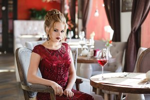 Elegant lady with glass of red wine in restaurant. Seductive young woman looking to camera