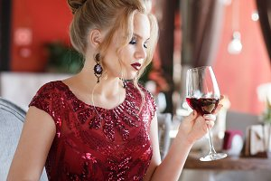 Elegant lady clothed in long red dress with glass of red wine in restaurant