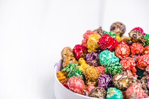 Brightly Colored Candied Popcorn, white background. Horizontal image of Junk food, fruit flavored popcorn in light pink bowl. Colorful, rainbow, candy coated popcorn. Shallow focus on popcorn in bowl.