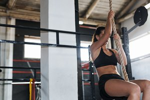Woman doing a rope climb exercise