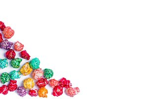 Brightly Colored Candied Popcorn, white background. Horizontal image of Junk food, fruit flavored popcorn in light pink bowl. Colorful, rainbow, candy coated popcorn. Shallow focus on popcorn in bowl. Isolated on white