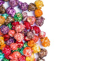 Brightly Colored Candied Popcorn, white background. Horizontal image of Junk food, fruit flavored popcorn. Colorful, rainbow, candy coated popcorn. Shallow focus on popcorn in bowl. Isolated on white selective focus and copyspace.