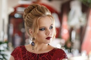 Elegant blonde lady in restaurant. Beautiful sexy young woman with long hair and pretty face make-up wearing evening dress in light luxury interior