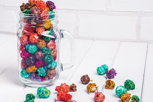 Brightly Colored Candied Popcorn, white background. Horizontal image of Junk food, fruit flavored popcorn in glass jar mason. Colorful, rainbow, candy coated popcorn. Shallow focus on popcorn in bowl. On the wooden table, selective focus and copyspace.