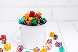 Brightly Colored Candied Popcorn, white background. Horizontal image of Junk food, fruit flavored popcorn in old metal cup. Colorful, rainbow, candy coated popcorn. On the wooden table, selective focus and copyspace