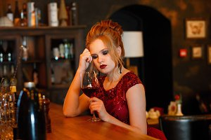 Portrait of gorgeous beauty young blonde woman in red dress sitting at the bar with glass of red wine in luxury interior
