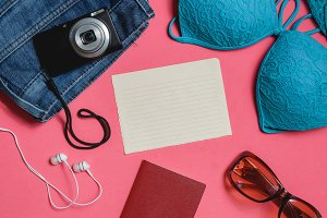 Blank Check list, Passport, Swimsuit, Jeans, Sunglasses, Photo Camera on Pink Background. Top View Travel Concept.