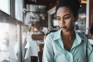Black pensive girl near window