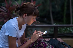 Young woman using smartphone outdoors at night time. Bali island.