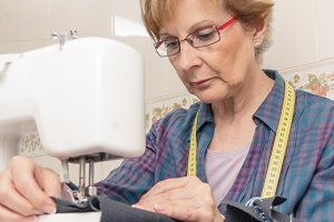 Senior seamstress on sewing machine