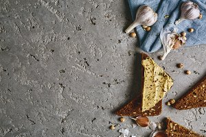 sliced whole wheat bread, chickpea and garlic on the grey concrete backdrop
