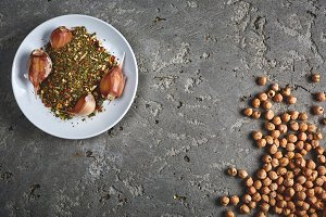 a plate of spices, chickpea and garlic on the grey concrete backdrop