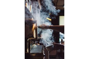 Close-up image of female barista using coffee-making machine to steam milk in cafe
