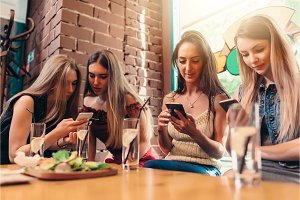 Four smiling female students sitting in cafeteria chatting using mobile phones